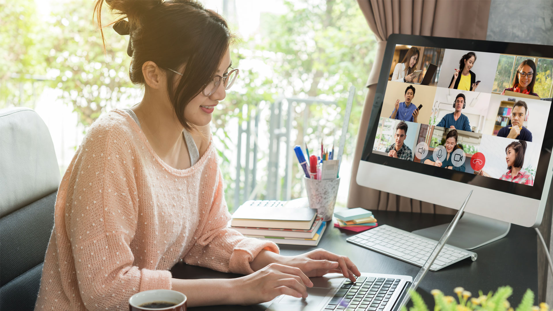 A female employee having a group video call on desktop simultaneously working on a laptop
